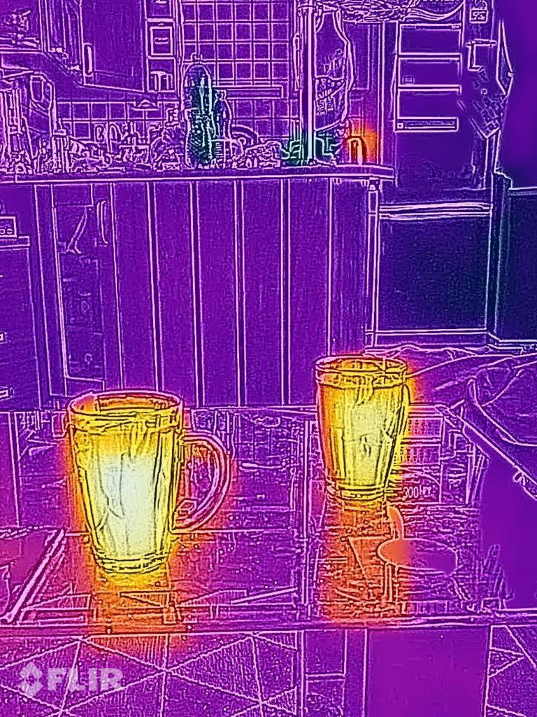 Dwa kubki zalane wrzątkiem. W tle na pomarańczowo - wciąż rozgrzany czajnik elektryczny
