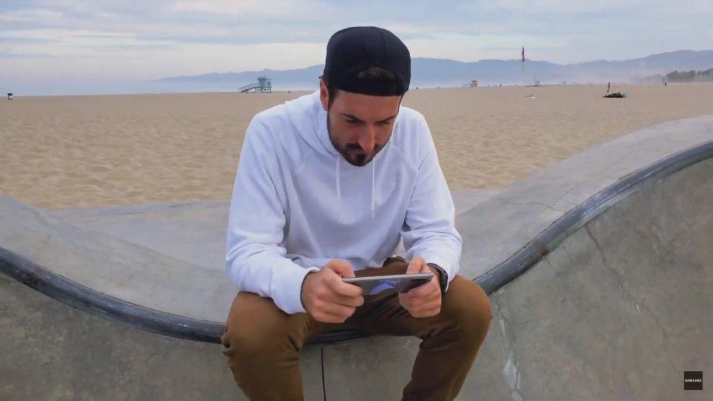 casey mc pery siedzi na murku i trzyma Samsunga Galaxy Note 10
