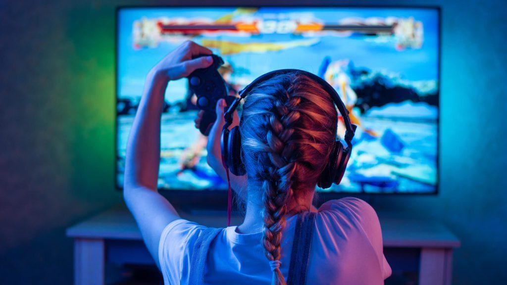 siedząca przed telewizorem dziewczynka z padem w ręku