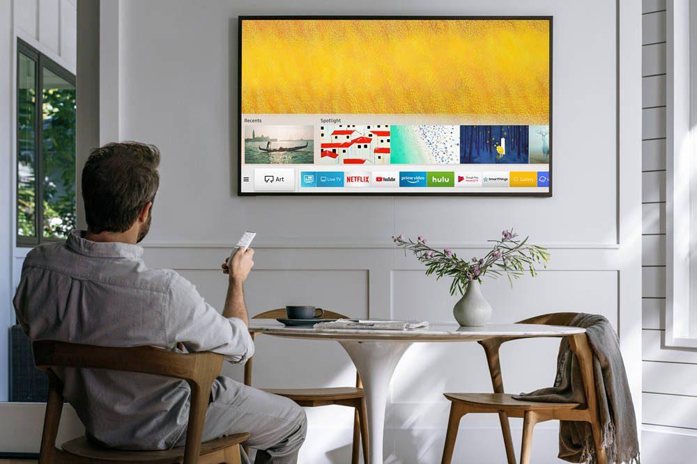 mężczyzna oglądający telewizję na ekranie powieszonym na ścianie