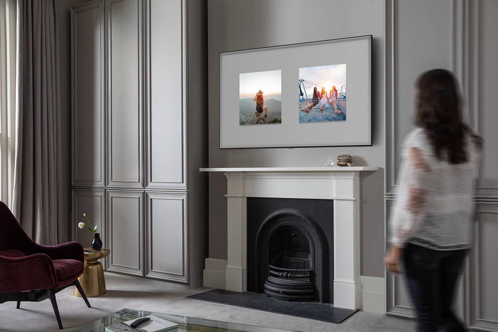 kobieta stojąca w salonie, w którym telewizor wisi na ścianie