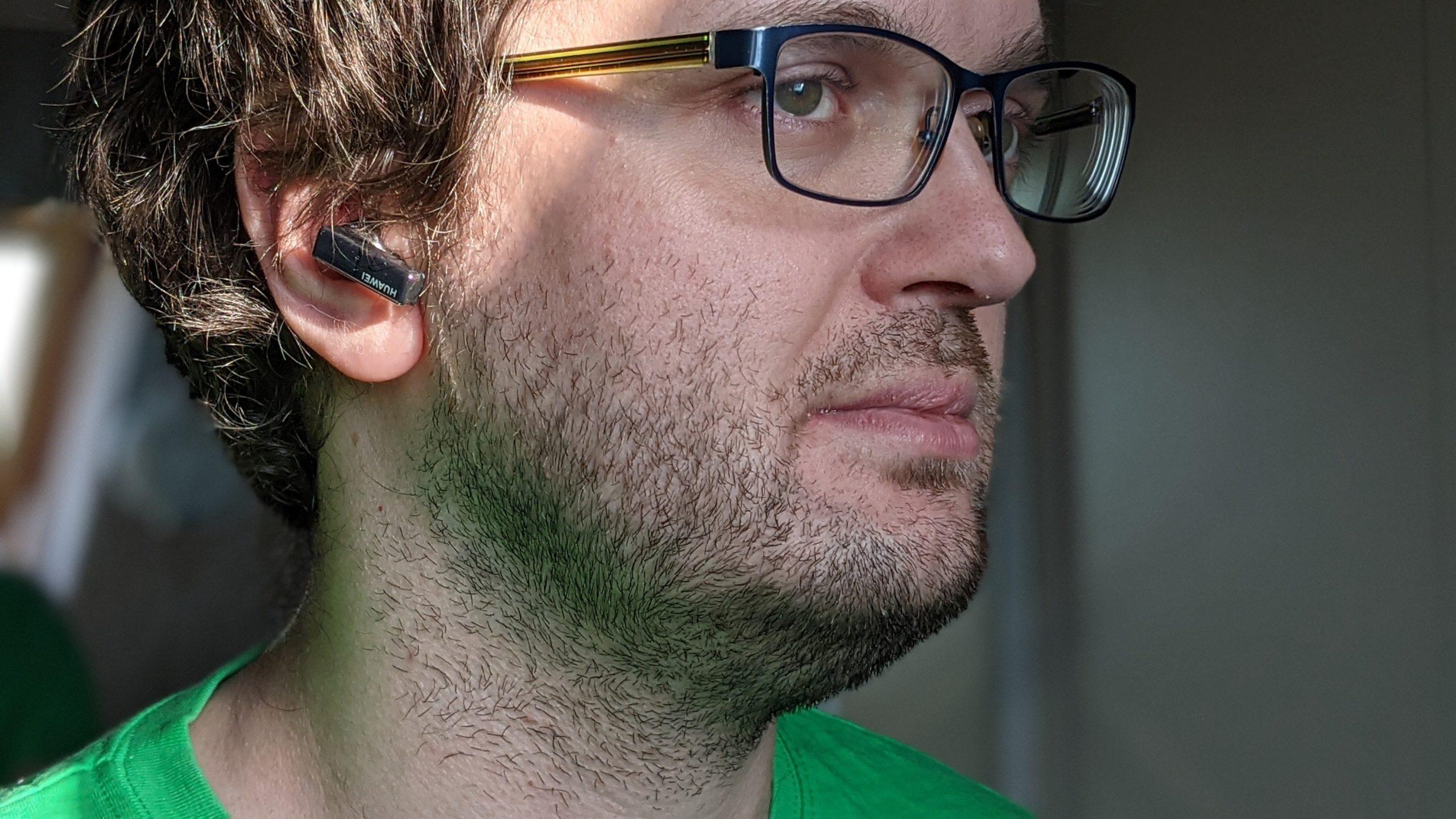 huawei freebuds pro w uchu niezbyt przystojnego chłopaka w zielonej koszulce