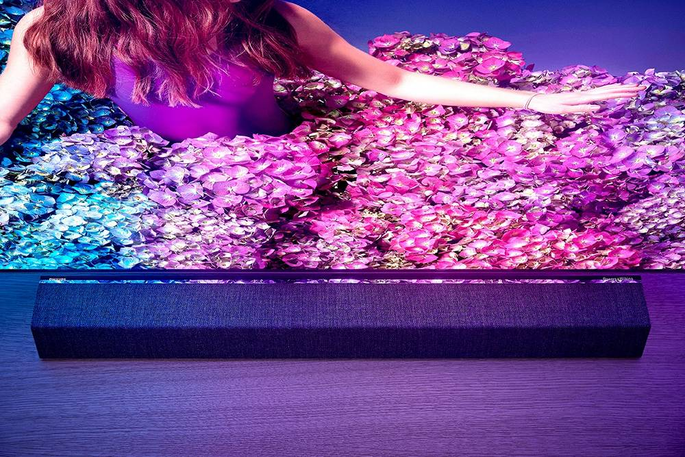 telewizor philips 65oled934 z soundbarem, na ekranie kolorowa scena utrzymana w odcieniach fioletu