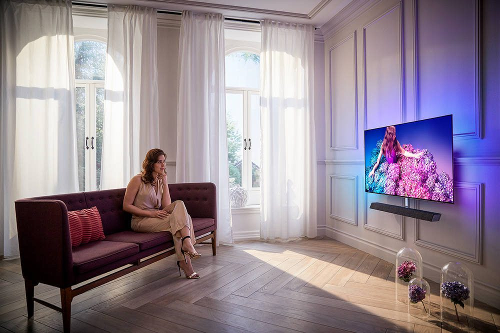 kobieta w ogląda telewizję na ekranie philipsa 65oled934