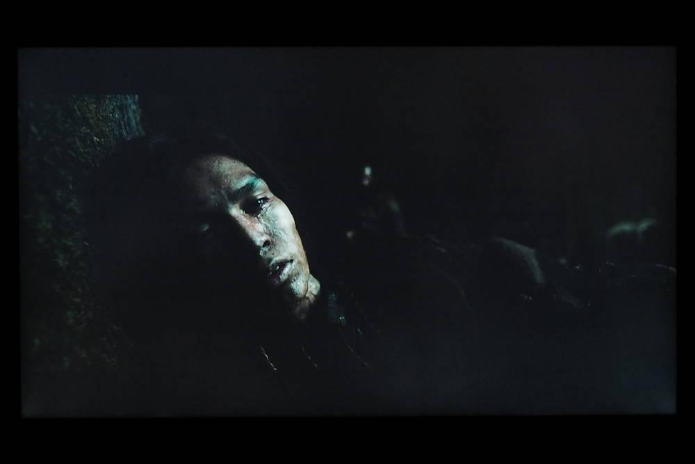 na ciemnym ekranie widać twarz leżącego mężczyzny, w tle delikatnie zarysowane drzewa i twarz innego mężczyzny