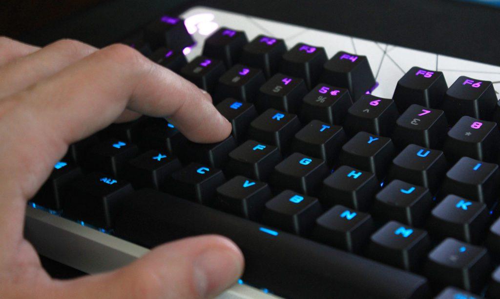 dłoń na klawiszach klawiatury logitech g pro kda