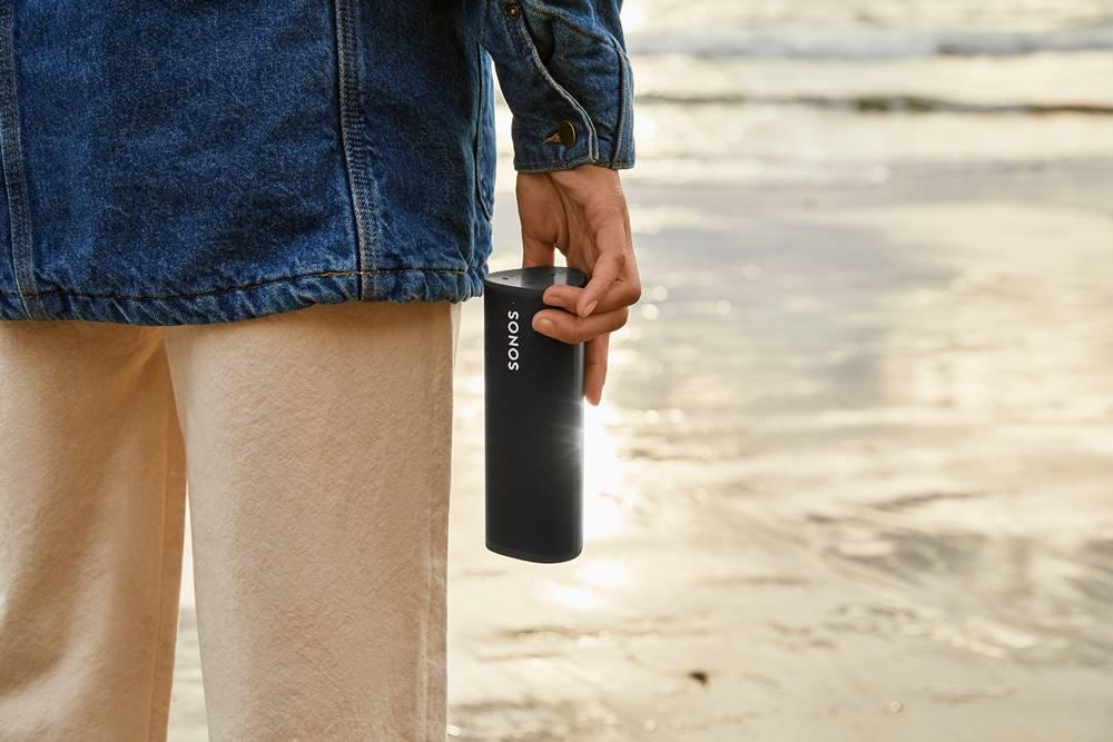 mężczyzna trzymający w dłoni głośnik sonos roam