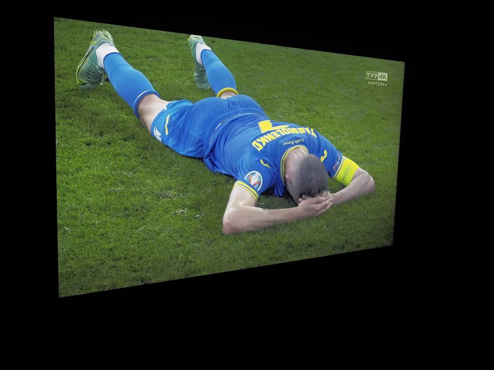 piłkarz w niebieskim stroju leży na murawie