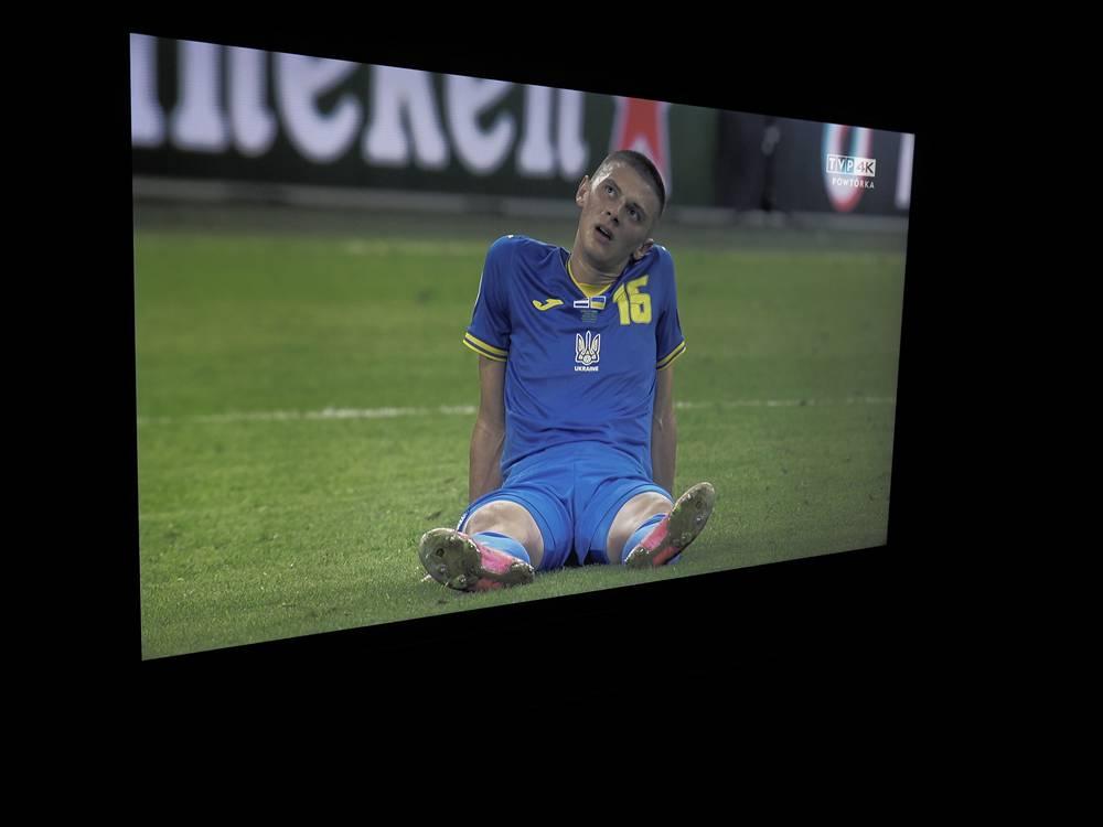 piłkarz siedzący na murawie