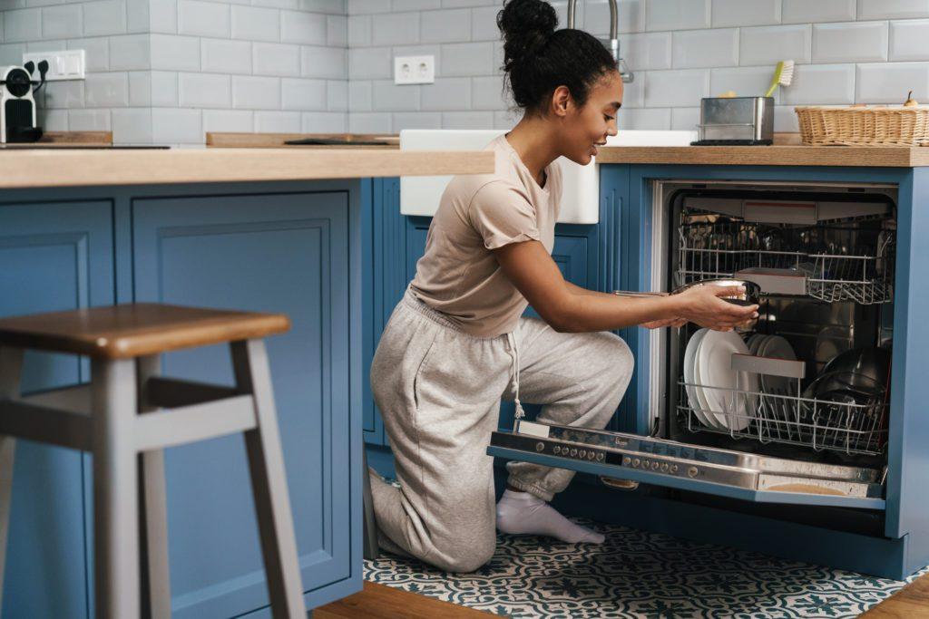 dziewczyna wkłada naczynia do zmywarki