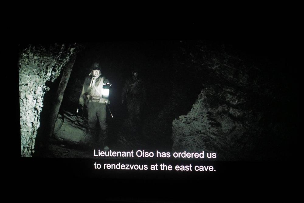 dwóch mężczyzn w jaskini, u dołu ekranu wyświetlają się napisy