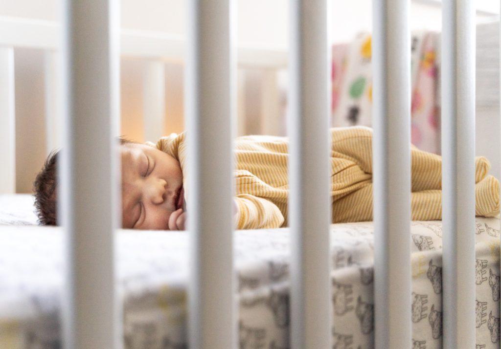dziecko śpi w łóżeczku